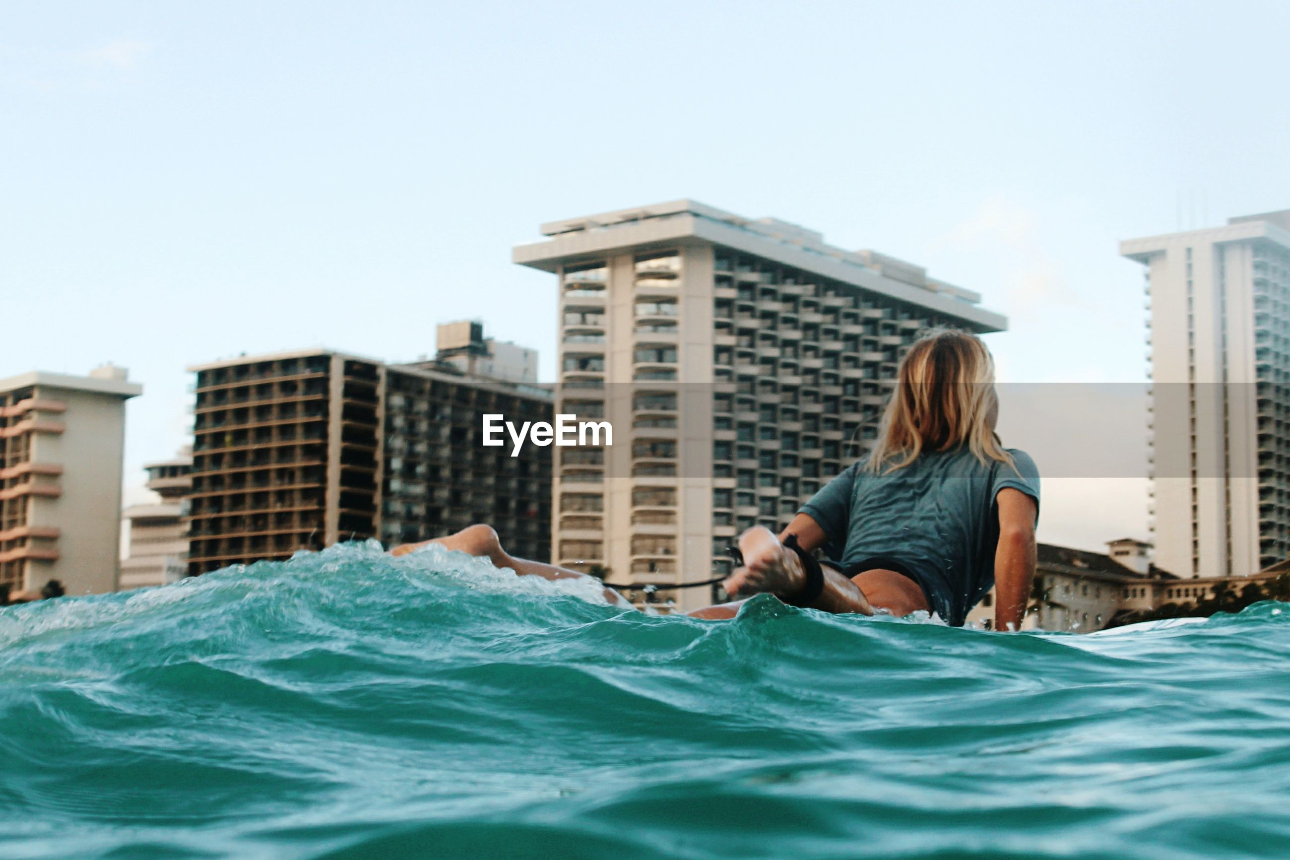 Low angle view of woman swimming in sea against buildings