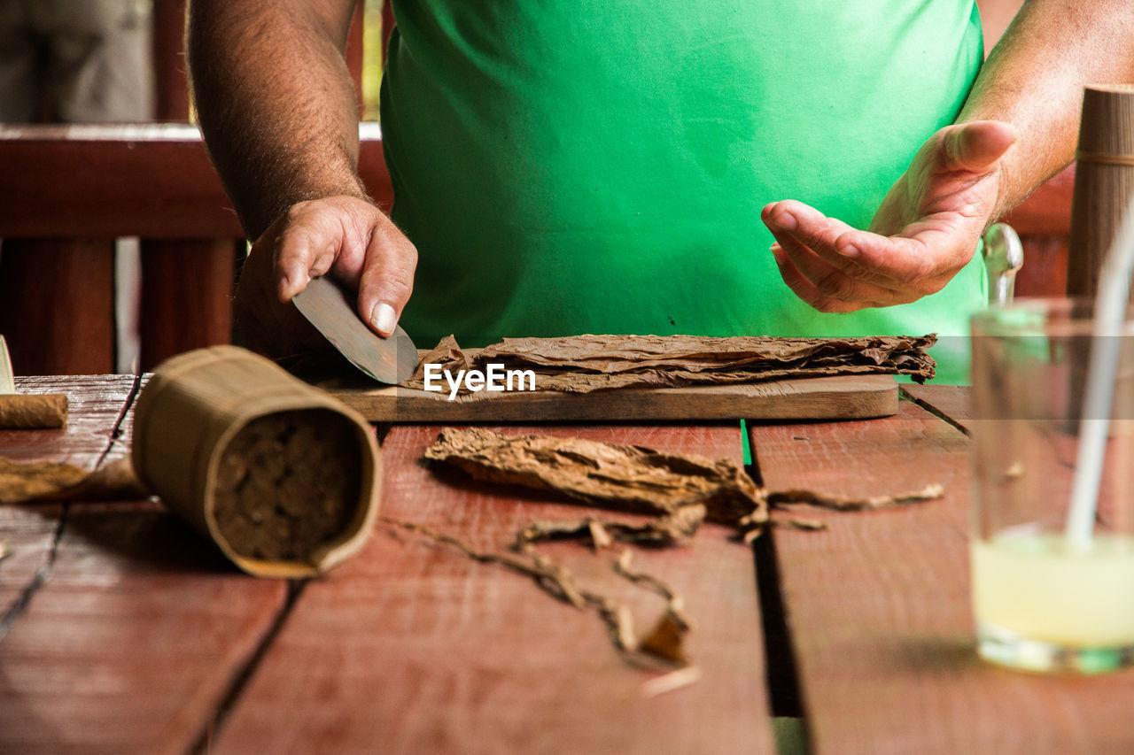 Close-Up Of Man Making Cigar