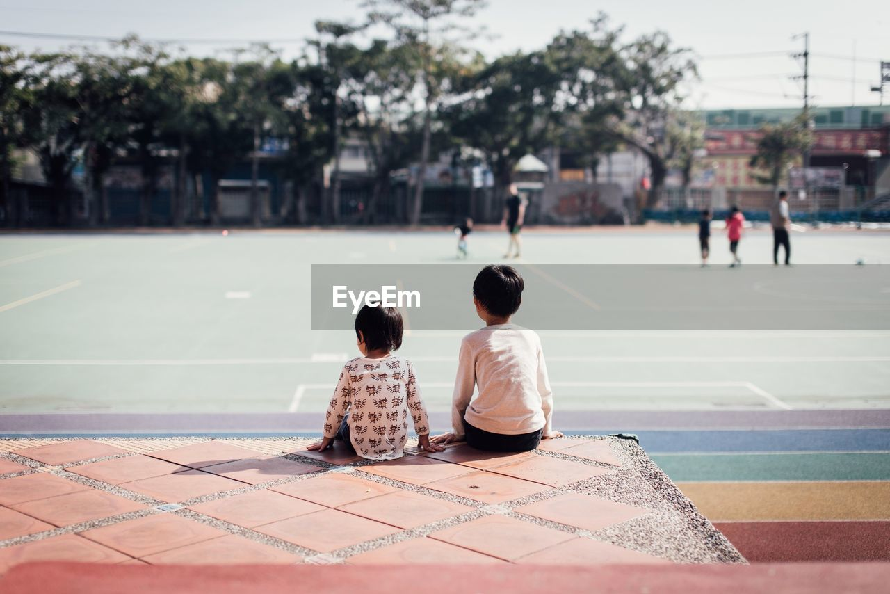 Rear view of siblings sitting at playground