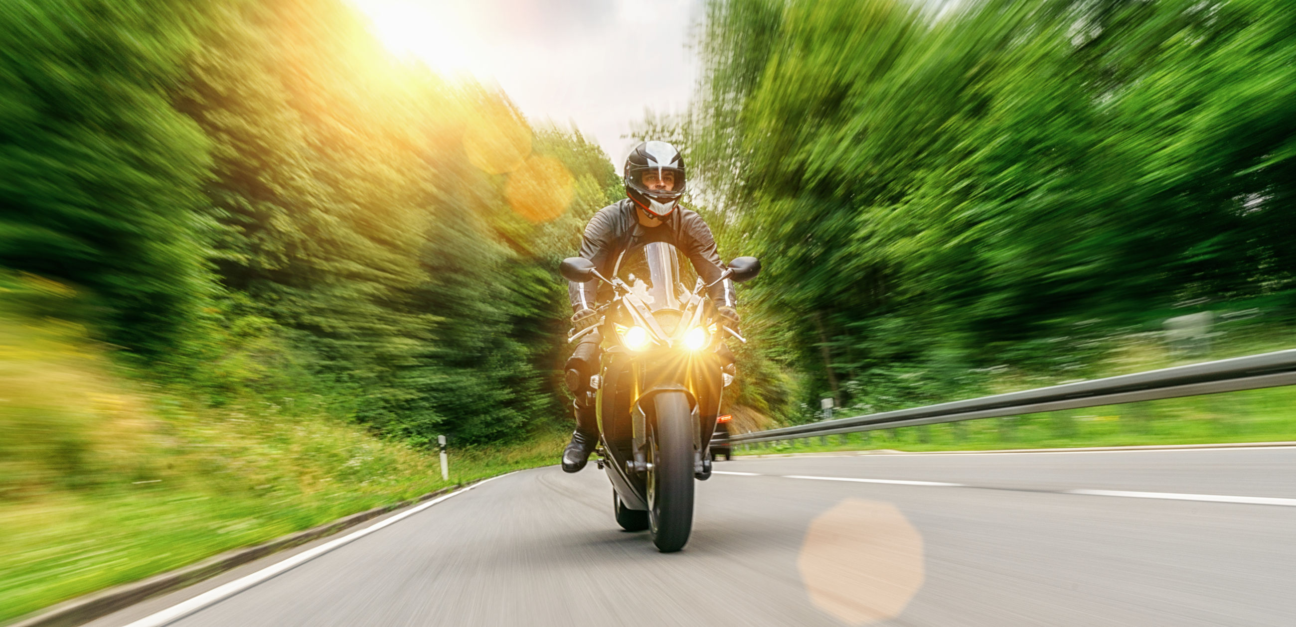 Man riding motorcycle on road against trees in forest
