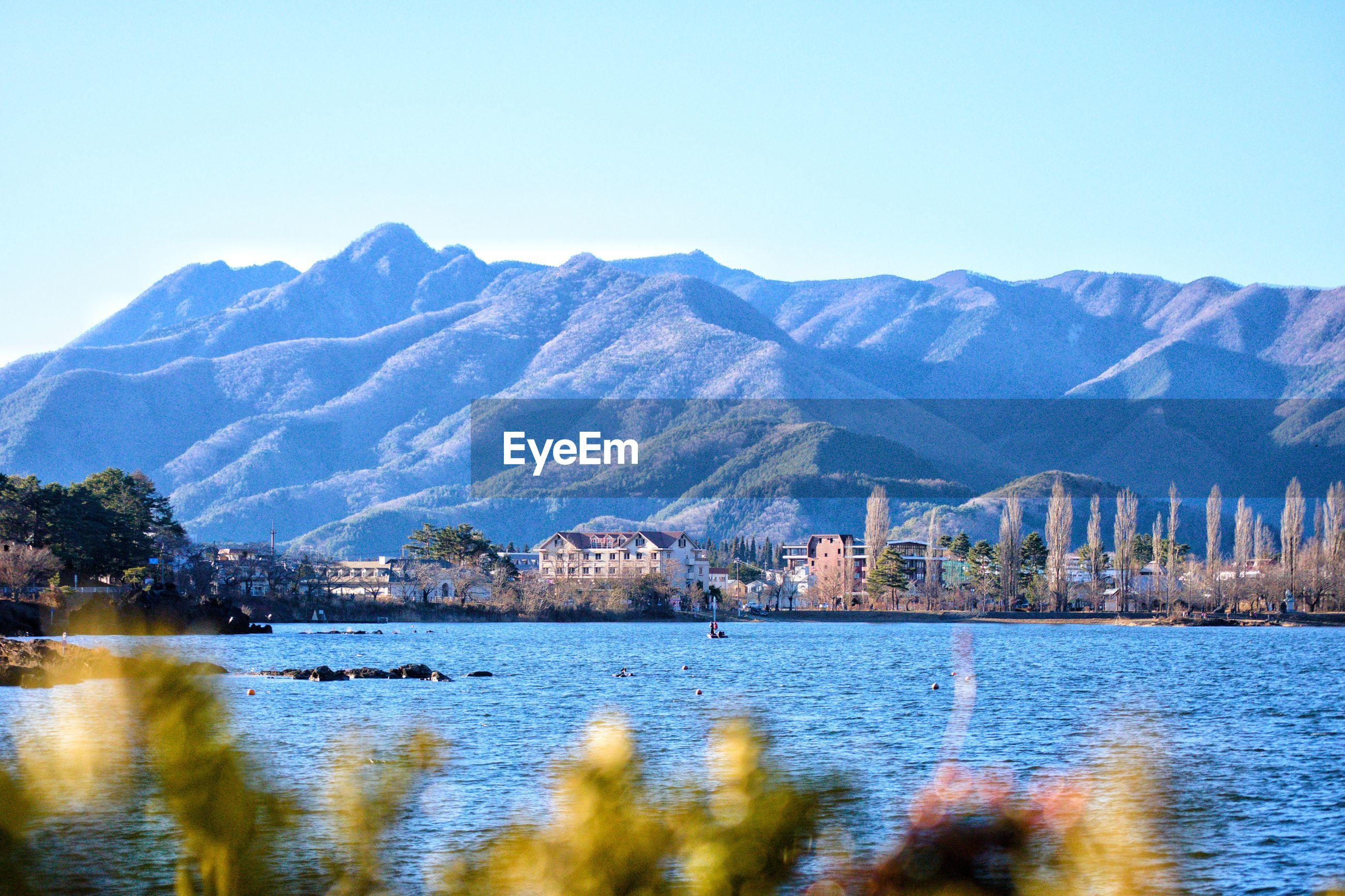 Scenic view of lake and buildings against clear sky