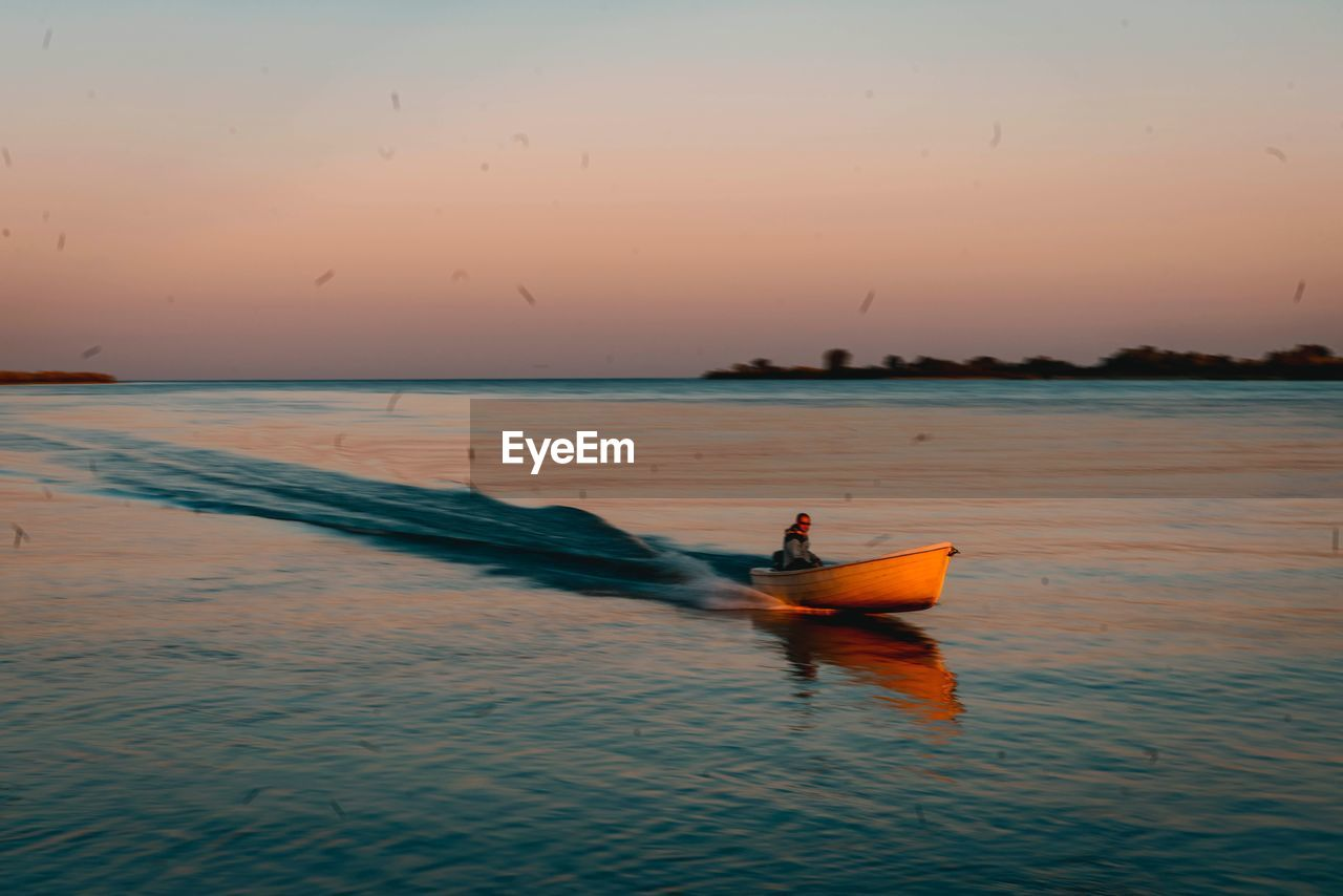 water, sunset, sky, nautical vessel, transportation, sea, waterfront, orange color, beauty in nature, mode of transportation, horizon over water, horizon, scenics - nature, real people, men, nature, tranquility, motion, people, outdoors