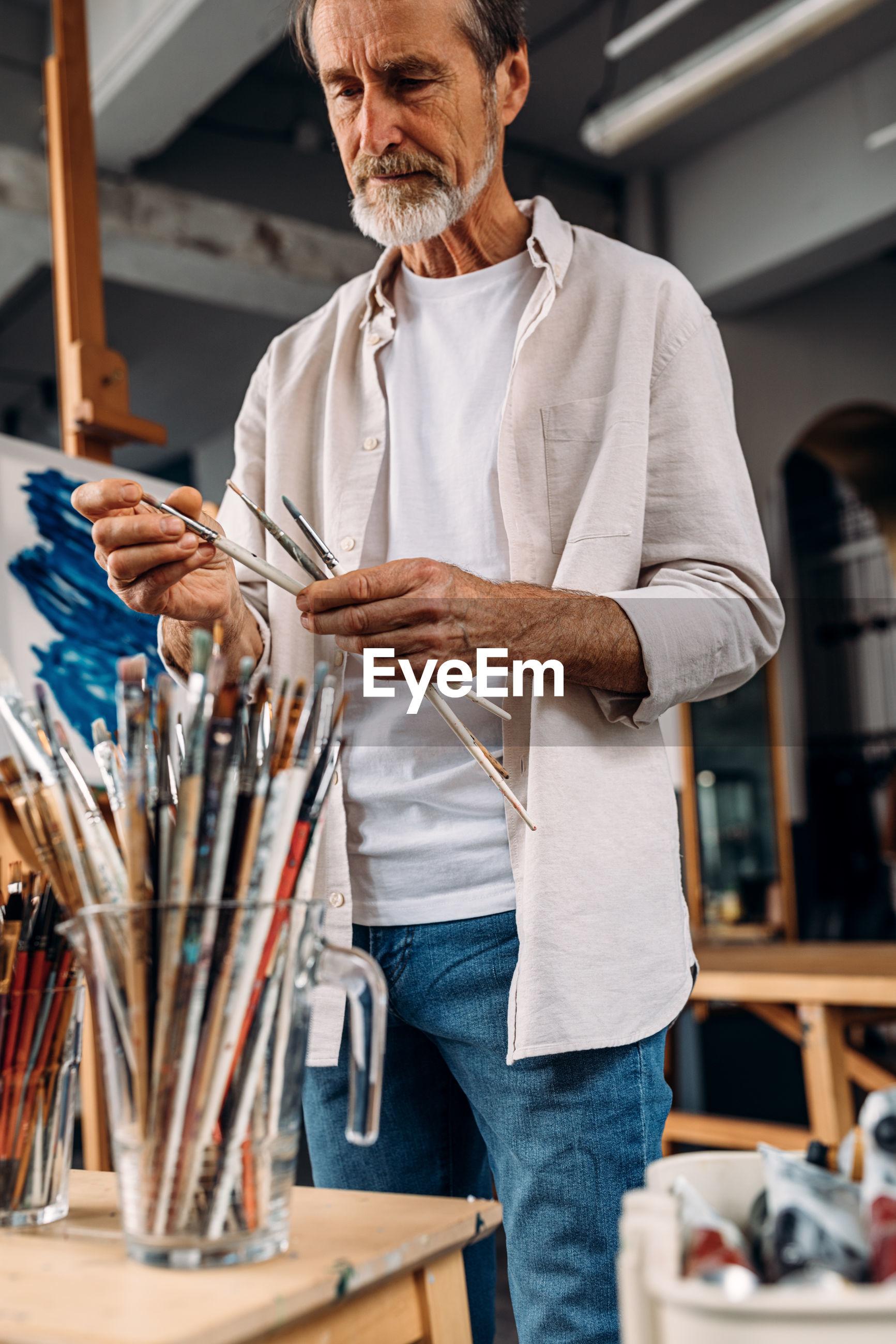 Senior man holding paintbrush while standing in workshop