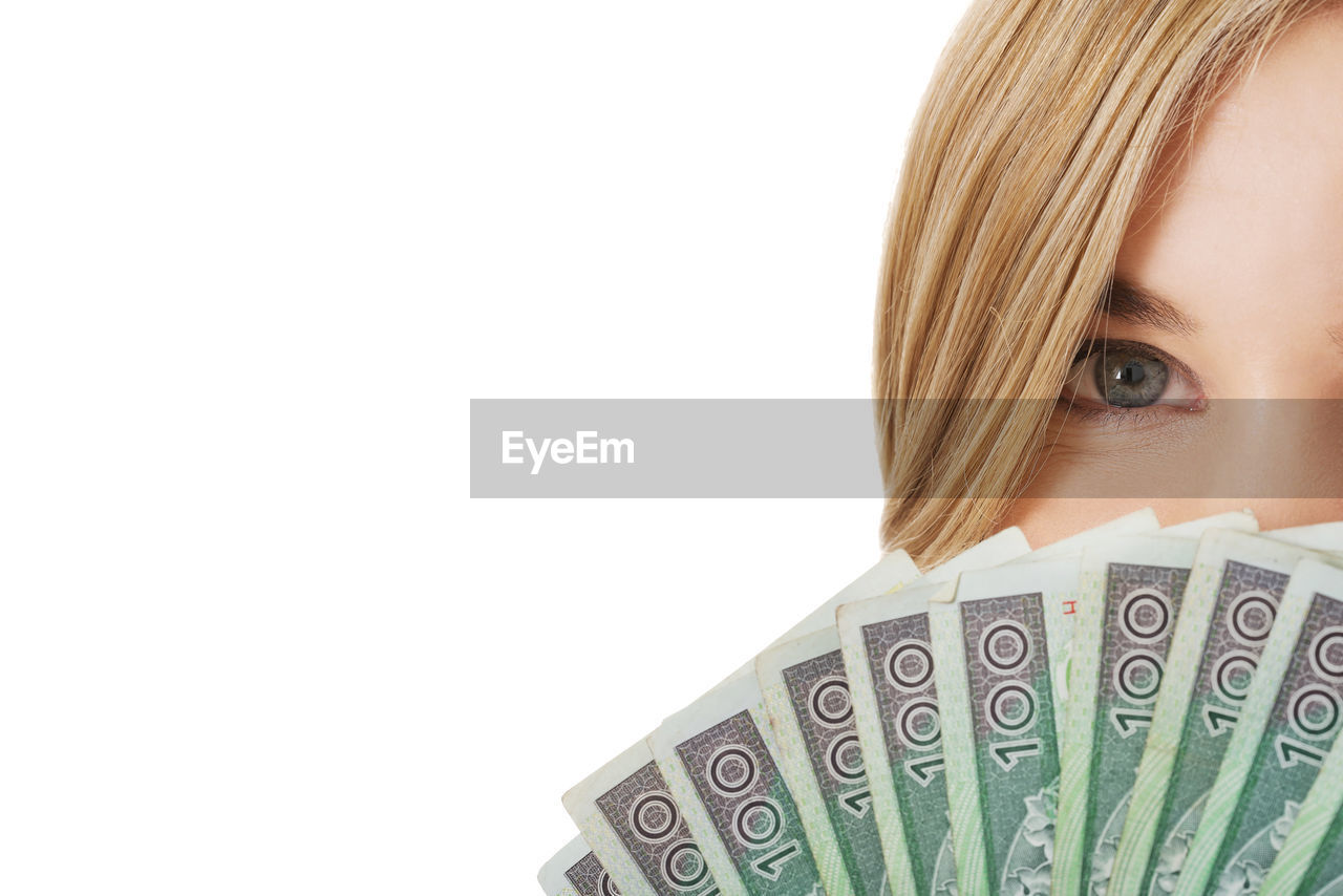 Portrait of young woman with fanned out paper currencies against white background