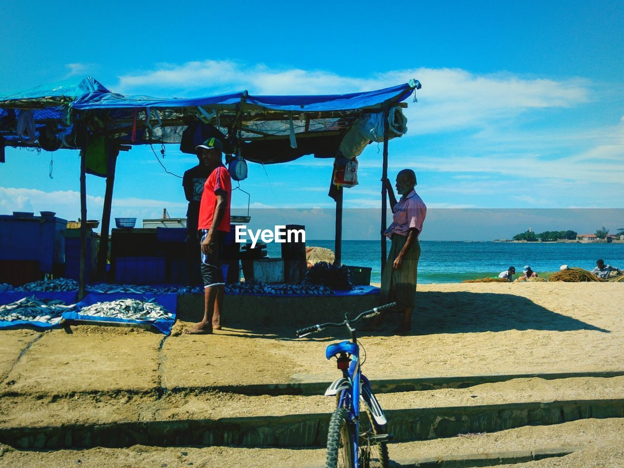 day, bicycle, sunlight, real people, beach, outdoors, shadow, mode of transport, sky, transportation, casual clothing, men, leisure activity, standing, lifestyles, full length, sand, nature, blue, sea, one person, people