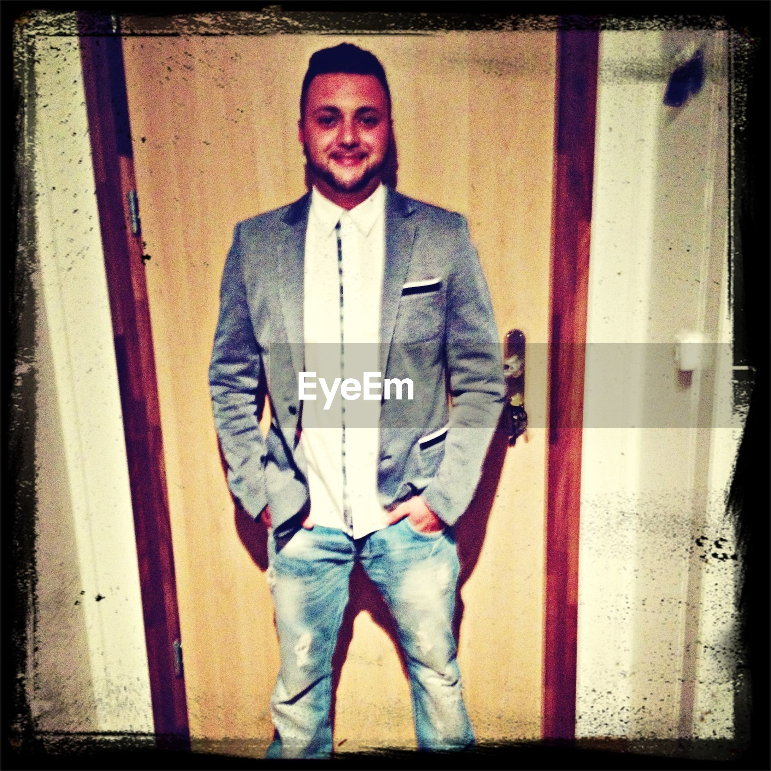 transfer print, person, auto post production filter, looking at camera, casual clothing, young adult, front view, lifestyles, portrait, standing, three quarter length, leisure activity, full length, young men, smiling, jacket, wall - building feature
