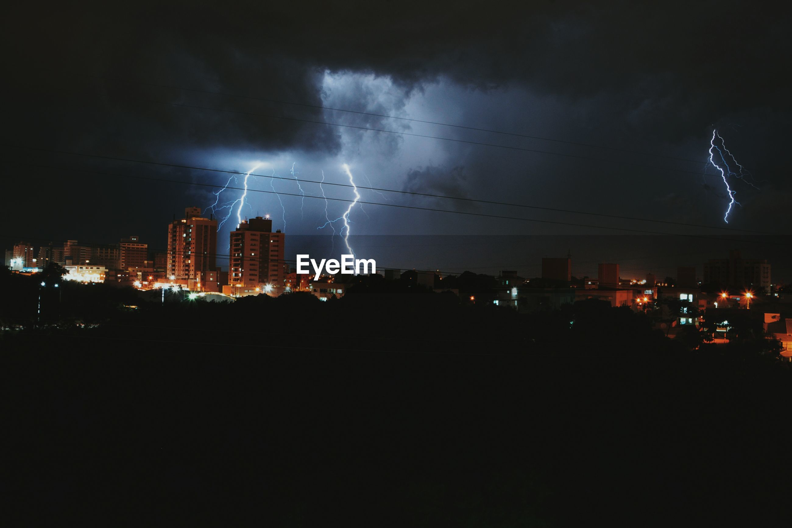 PANORAMIC VIEW OF ILLUMINATED CITY AGAINST STORM AT NIGHT