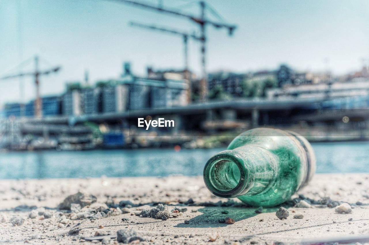 water, focus on foreground, architecture, building exterior, no people, nature, sea, built structure, sky, day, close-up, city, outdoors, container, transportation, land, clear sky, nautical vessel
