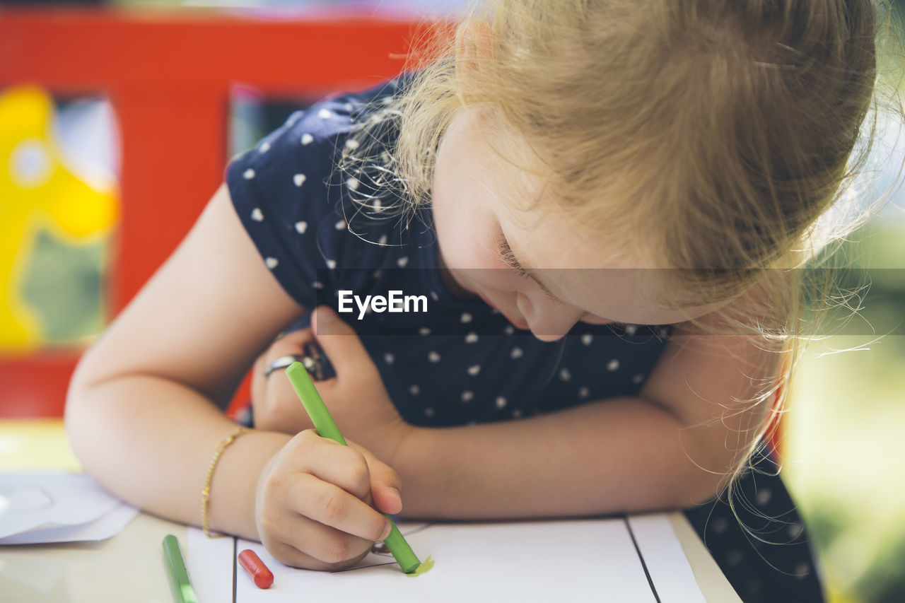 Close-Up Of Girl Drawing With Crayon