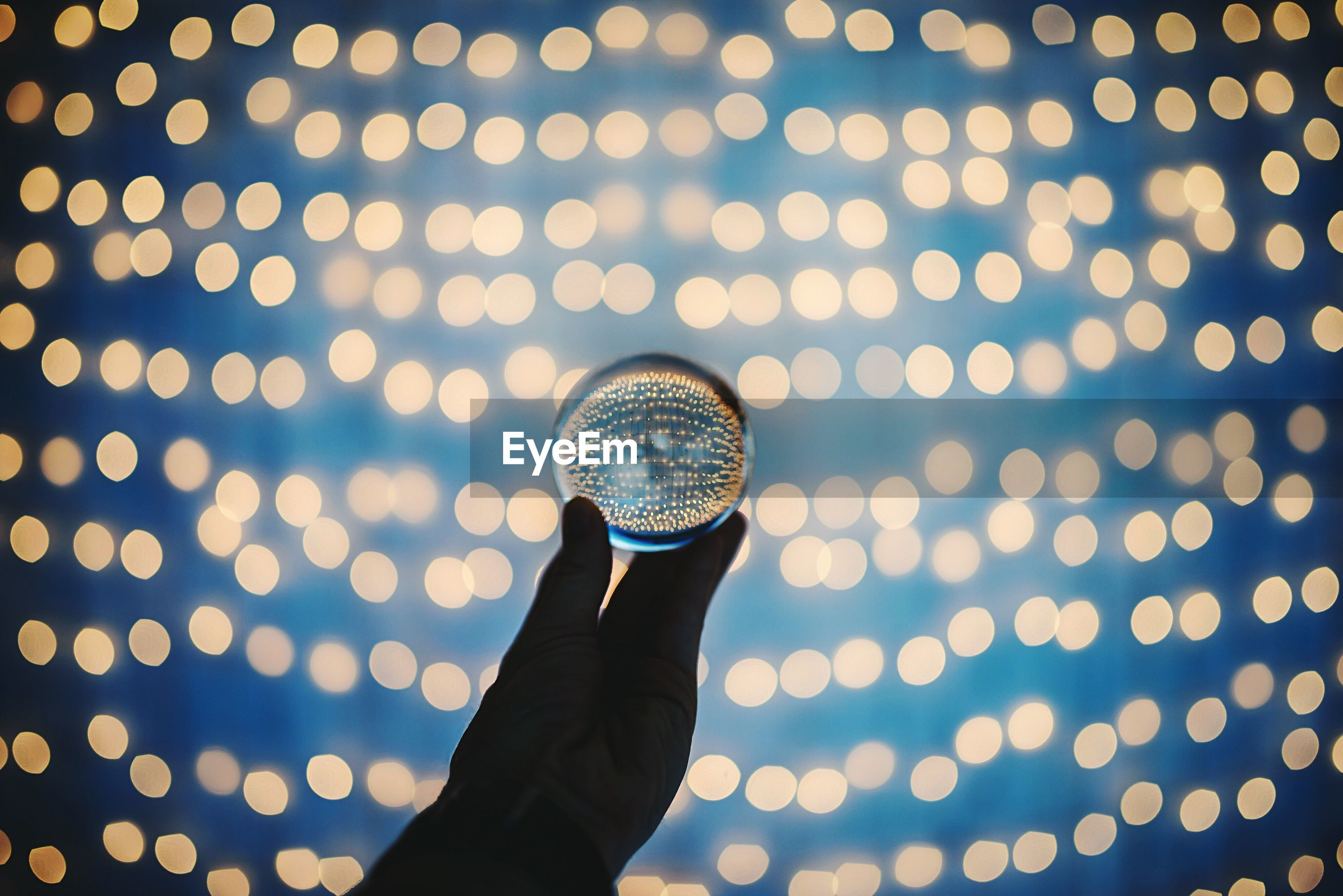 Close-up of gloved hand holding glass ball