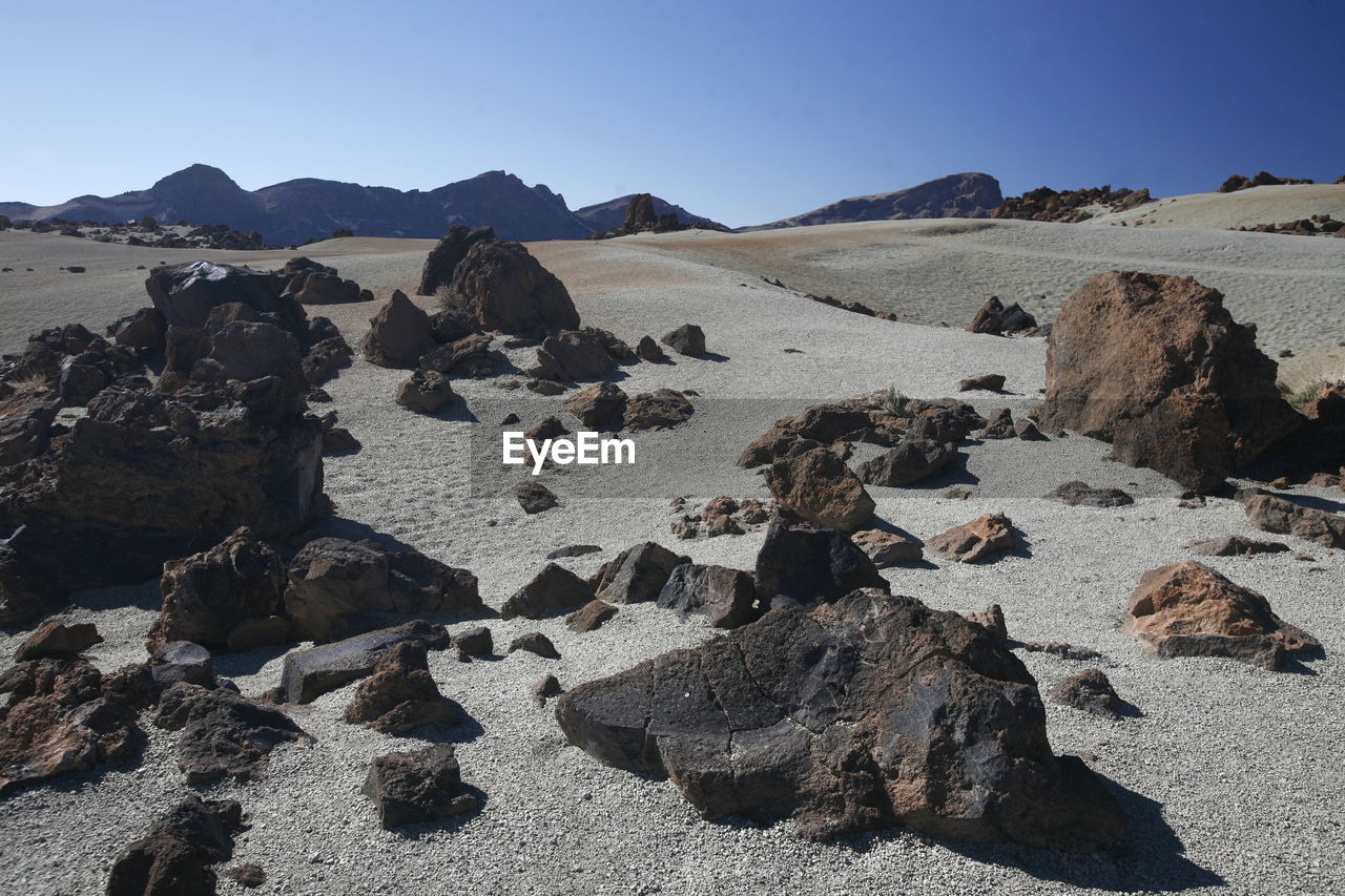 Tranquil View Of Rocks On Field Against Blue Sky