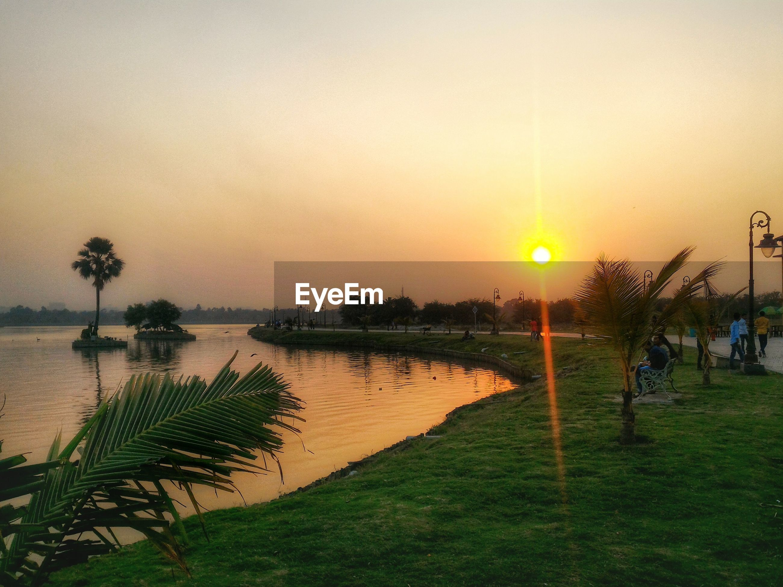 People relaxing at park by lake against clear sky during sunset