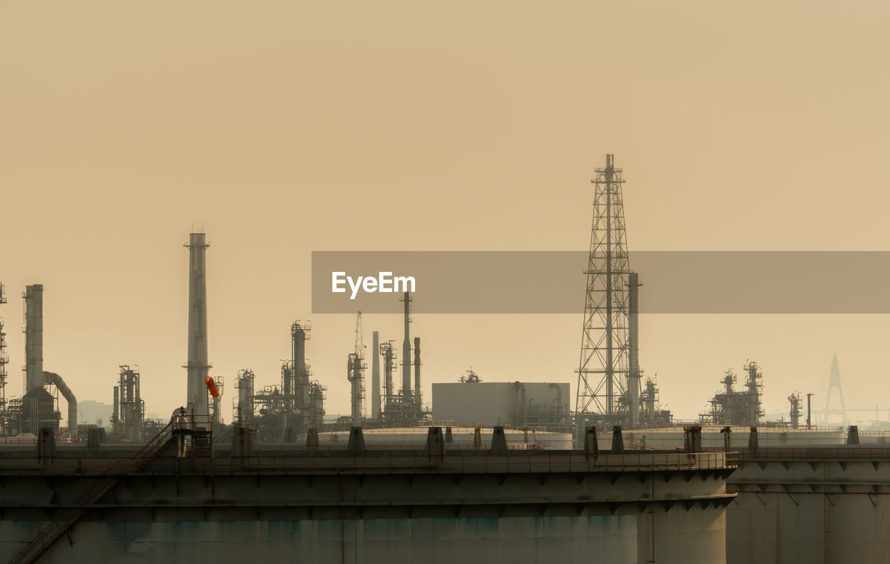 built structure, building exterior, architecture, sky, industry, factory, fuel and power generation, smoke stack, clear sky, nature, no people, sunset, industrial building, copy space, development, environmental issues, outdoors, tall - high, water, pollution, industrial district, air pollution