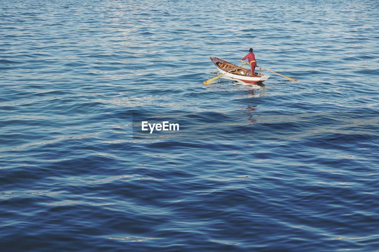 Man Paddling In Sea