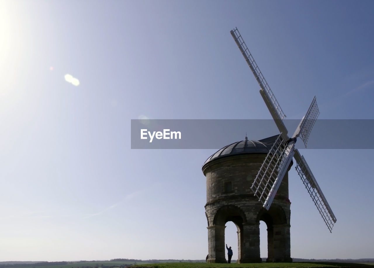 Small Windmill On Field Against Sky