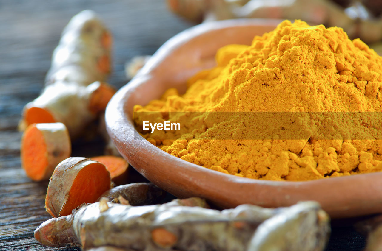 food and drink, food, spice, ground - culinary, close-up, yellow, ingredient, freshness, turmeric, still life, wood - material, wellbeing, focus on foreground, healthy eating, no people, kitchen utensil, table, indoors, eating utensil, raw food