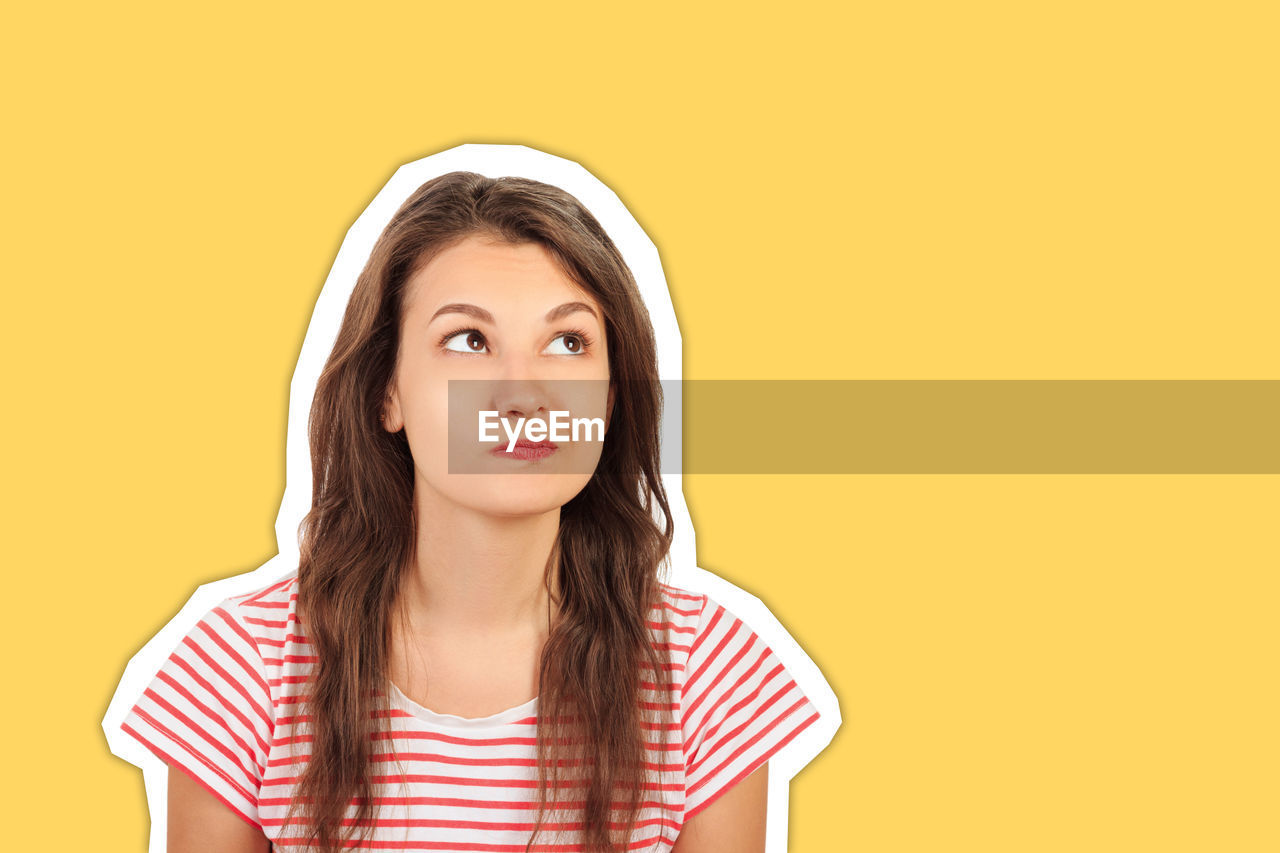 Young woman making face against yellow background