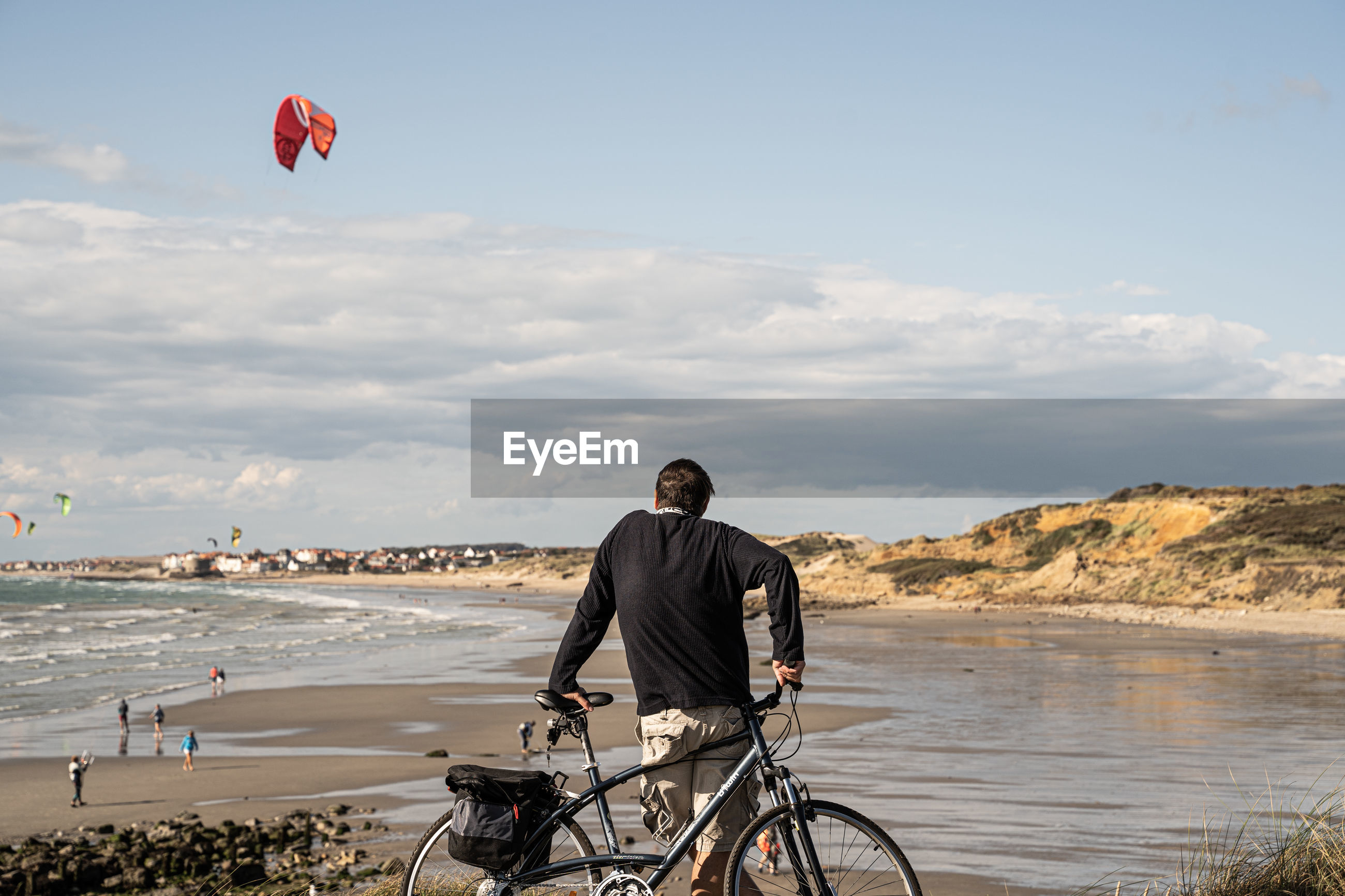 MAN WITH BICYCLE AT BEACH AGAINST SKY