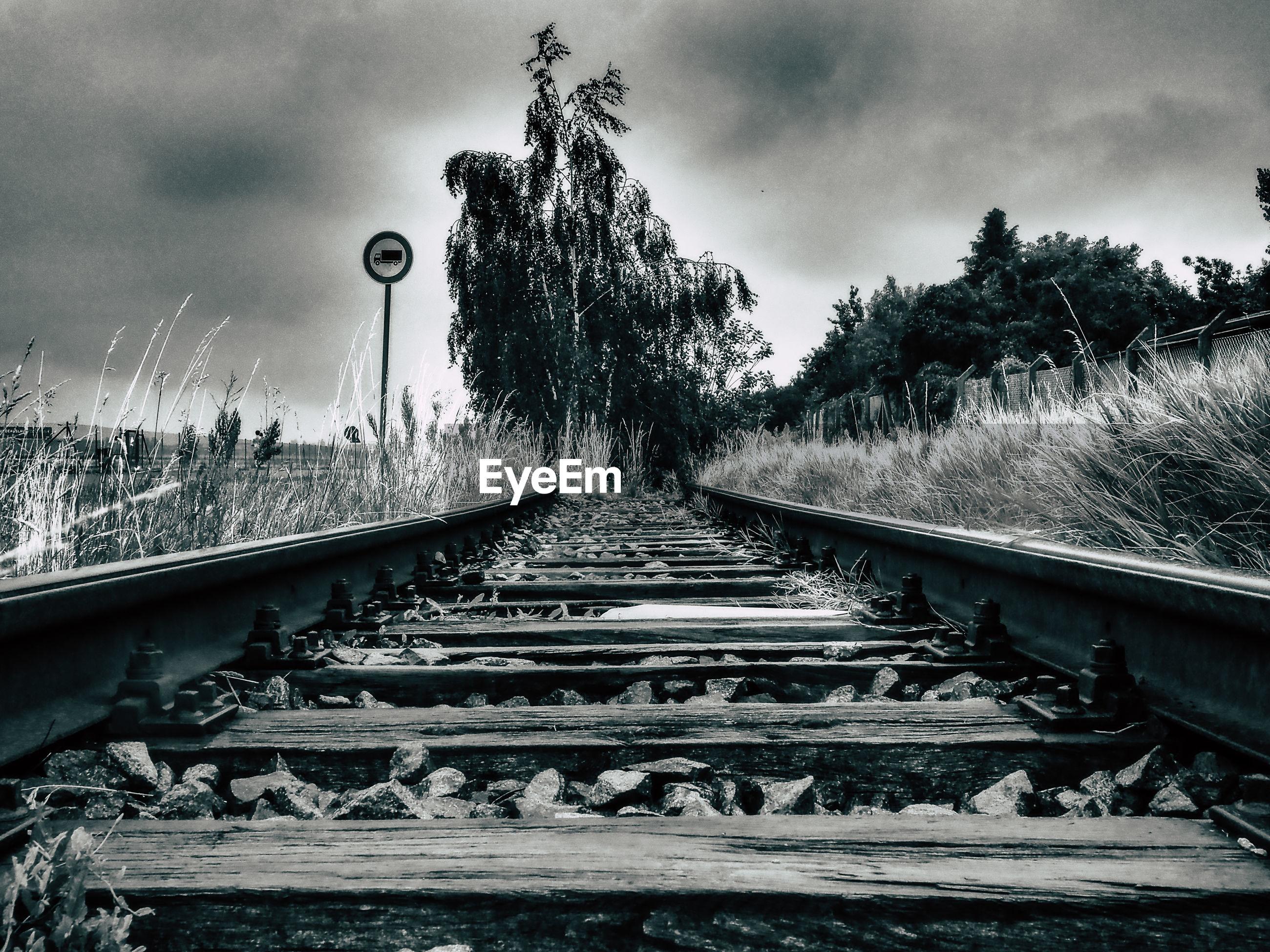 Abandoned railroad track amidst field