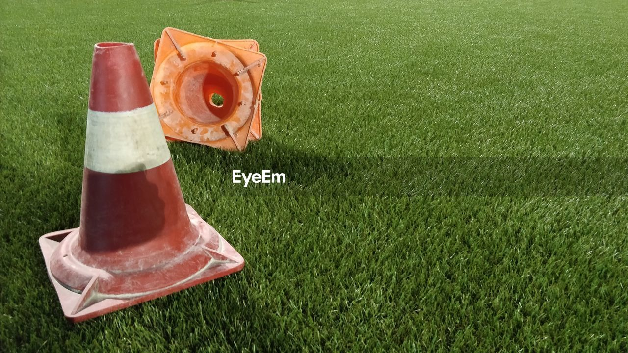 grass, plant, nature, no people, green color, traffic cone, orange color, cone, sport, day, high angle view, outdoors, field, land, red, lawn, food and drink, close-up, copy space, protection