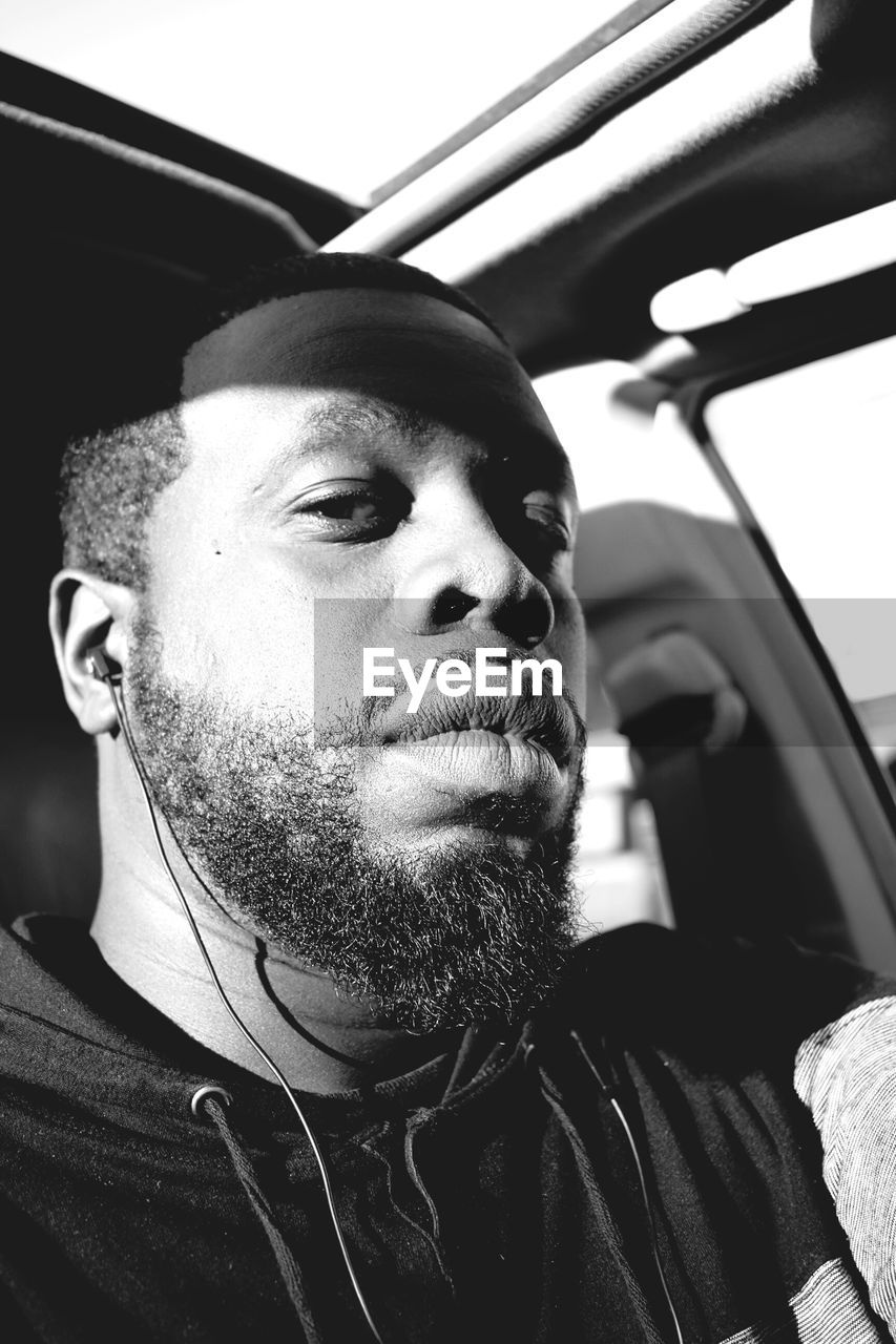 Close-up portrait of man listening music while sitting in car