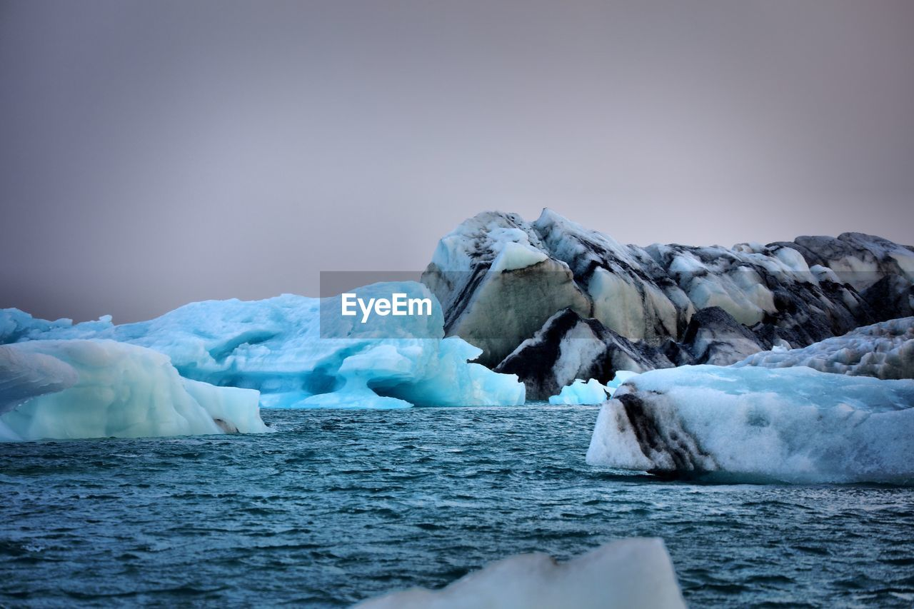 Scenic View Of Icebergs In Water Against Sky