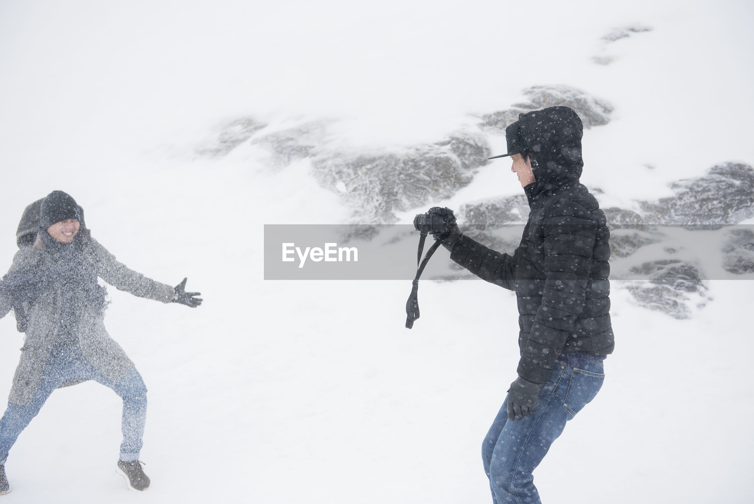Man photographing friend on snow covered field