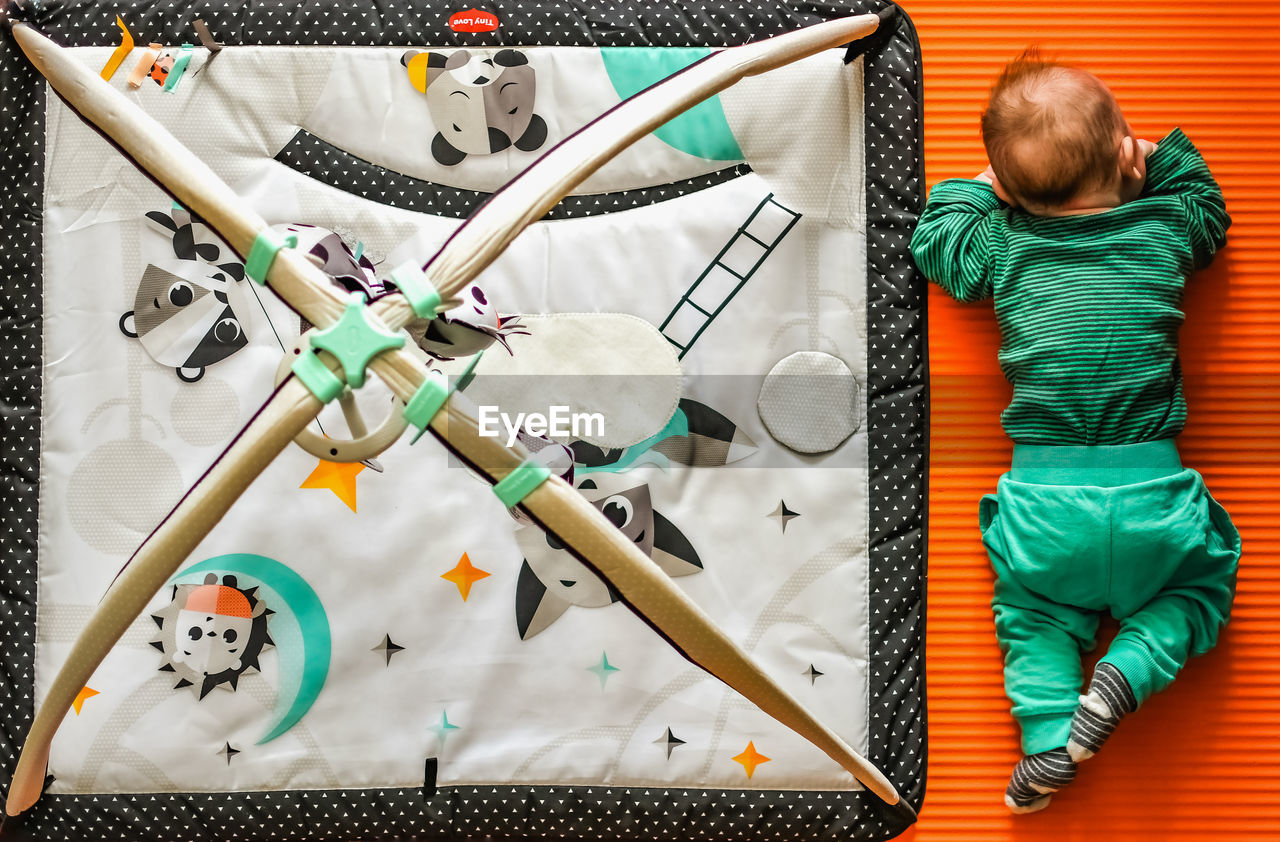 HIGH ANGLE VIEW OF BOY WITH TOY ON TABLE