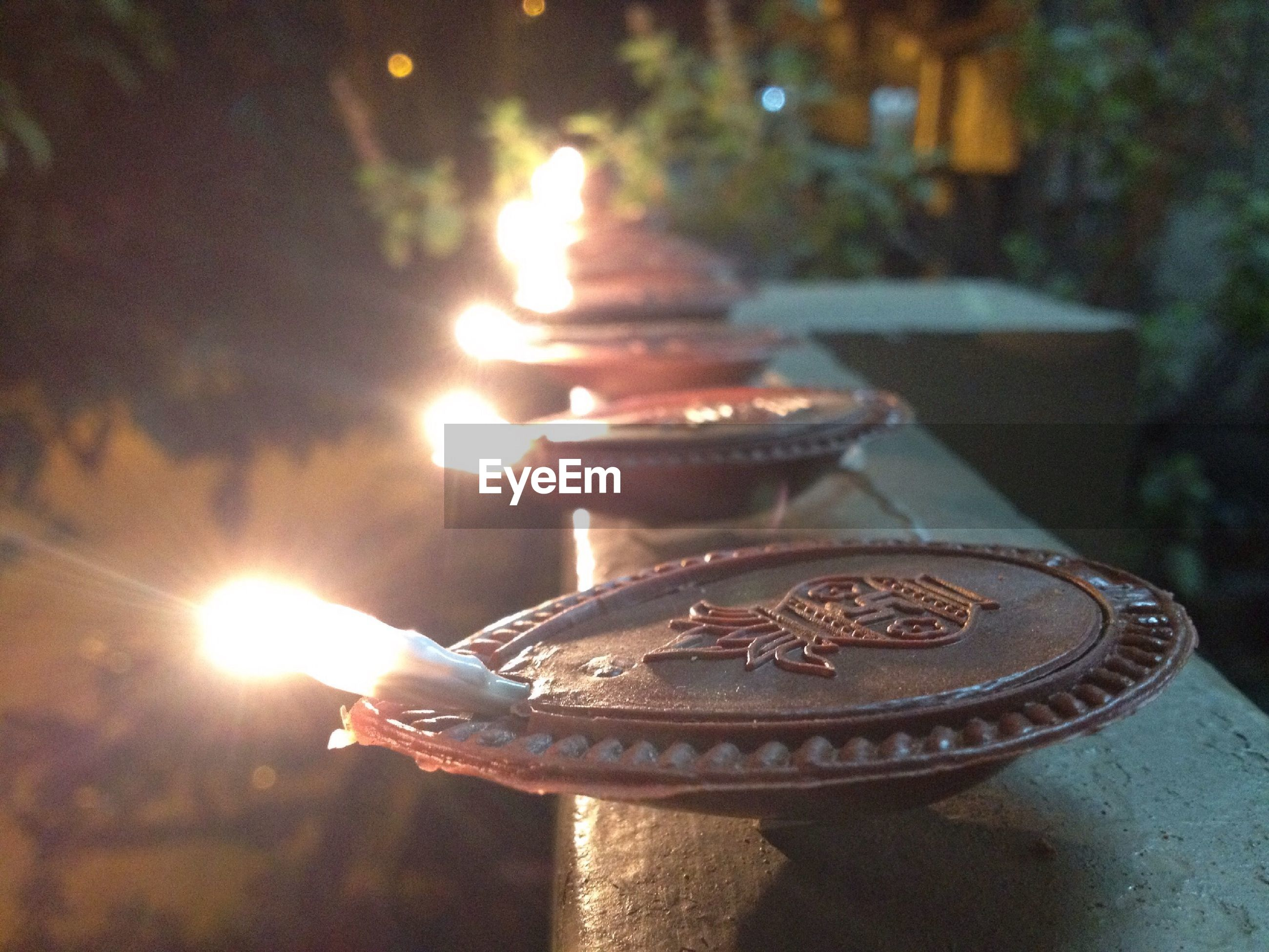 illuminated, close-up, focus on foreground, flame, burning, glowing, indoors, candle, religion, fire - natural phenomenon, no people, night, spirituality, metal, heat - temperature, orange color, still life, shiny, selective focus