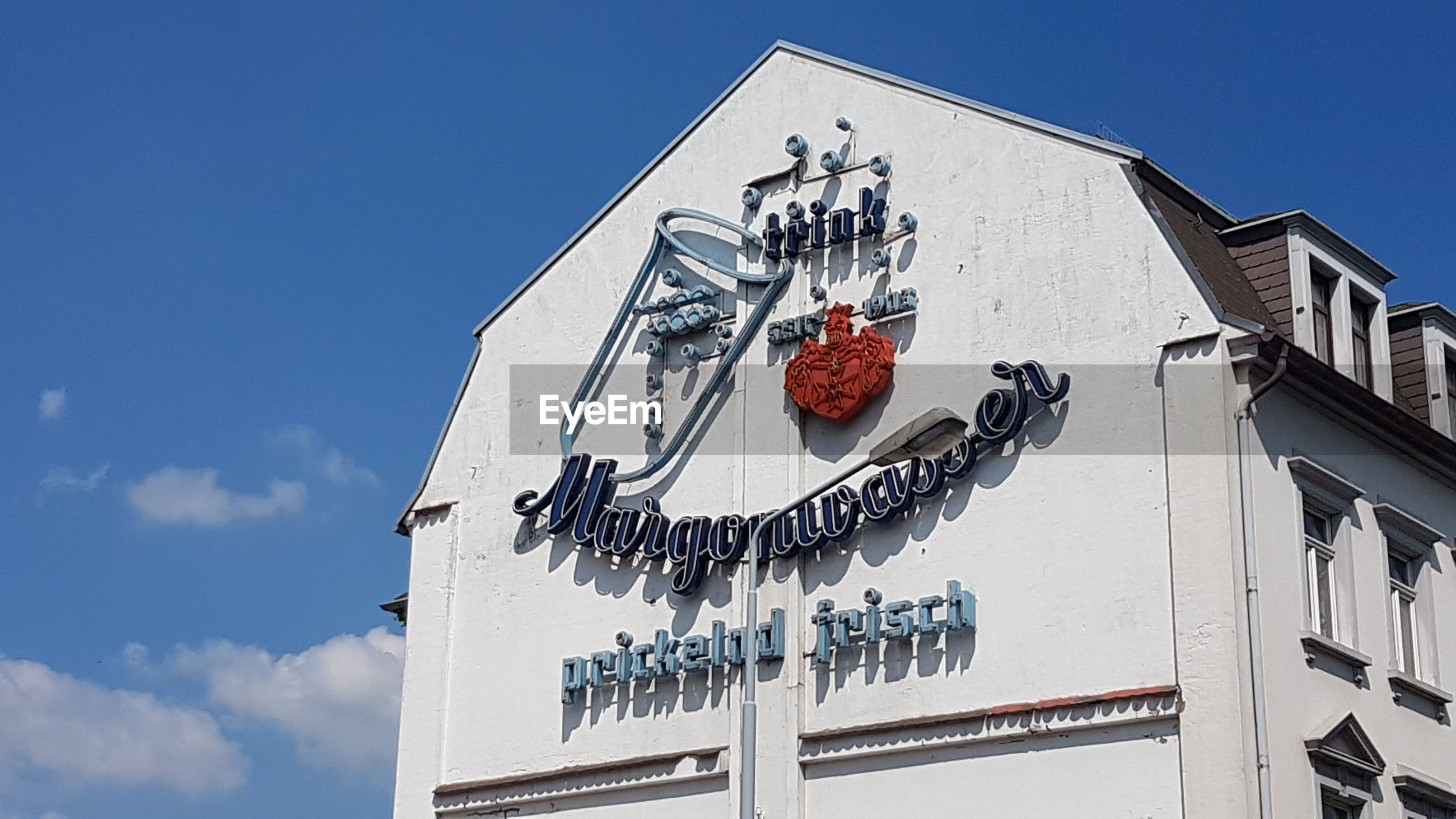 built structure, building exterior, architecture, low angle view, sky, text, communication, nature, day, no people, building, blue, sunlight, western script, representation, art and craft, outdoors, sign, creativity, white color