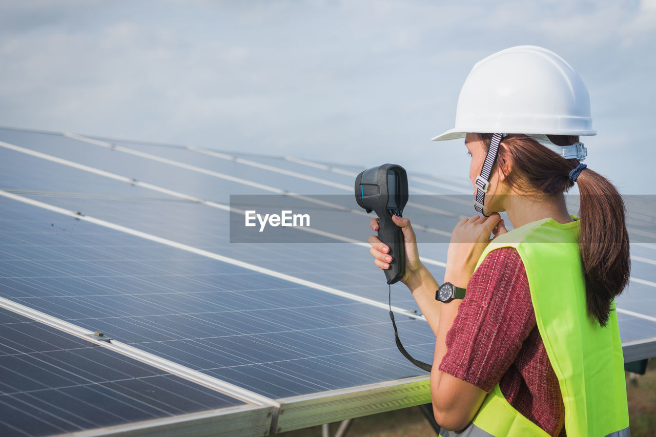 technology, solar energy, solar panel, environmental conservation, sky, real people, alternative energy, adult, women, lifestyles, renewable energy, fuel and power generation, holding, one person, environment, occupation, nature, day, young adult, outdoors, electricity, power supply, sustainable resources