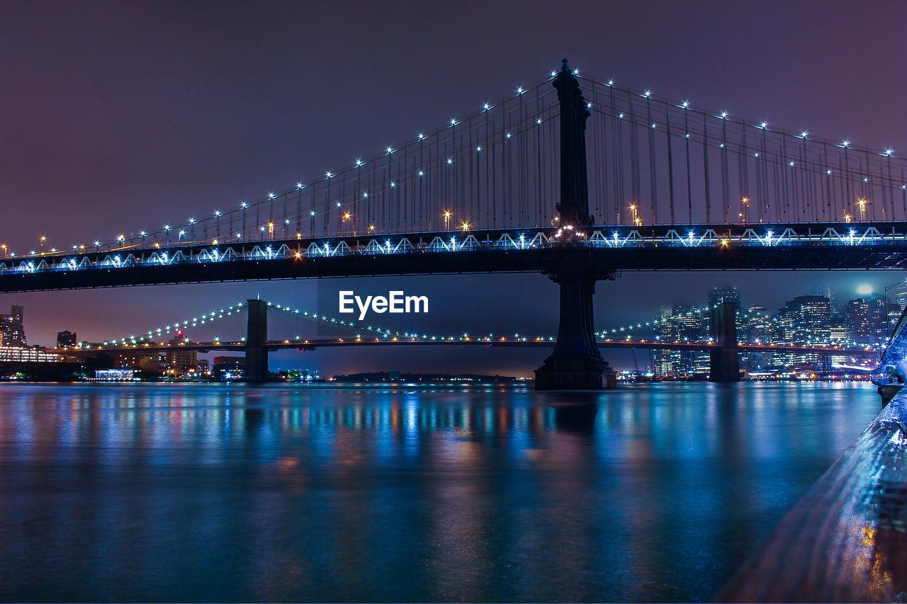 Manhattan bridge over river against sky at night