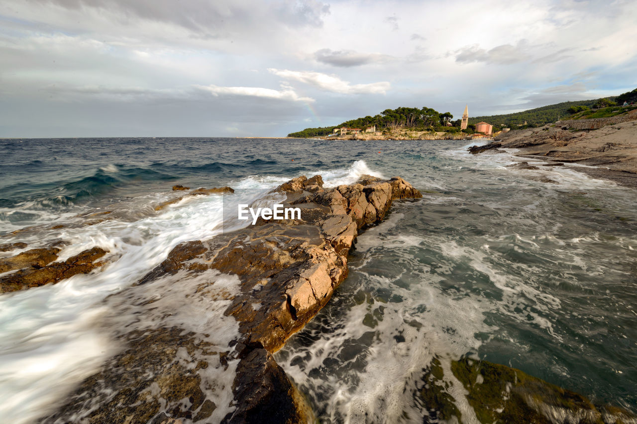 sea, water, sky, beauty in nature, scenics - nature, motion, cloud - sky, rock, sport, rock - object, solid, surfing, aquatic sport, land, nature, beach, horizon, wave, horizon over water, outdoors