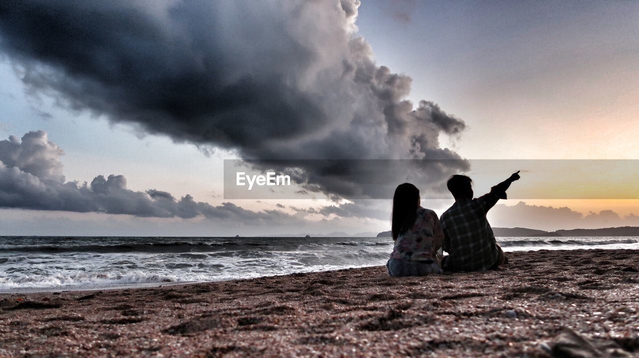 sea, sky, cloud - sky, two people, beach, horizon over water, real people, nature, water, togetherness, sunset, beauty in nature, men, outdoors, leisure activity, scenics, lifestyles, sand, silhouette, bonding, vacations, full length, day, wave, people