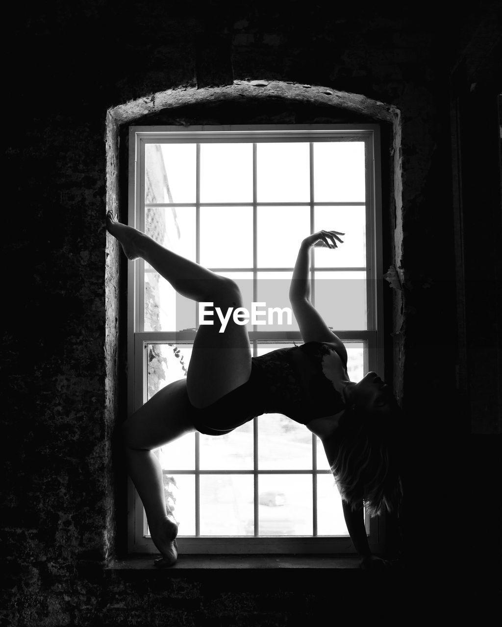 WOMAN LOOKING THROUGH WINDOW IN MIRROR