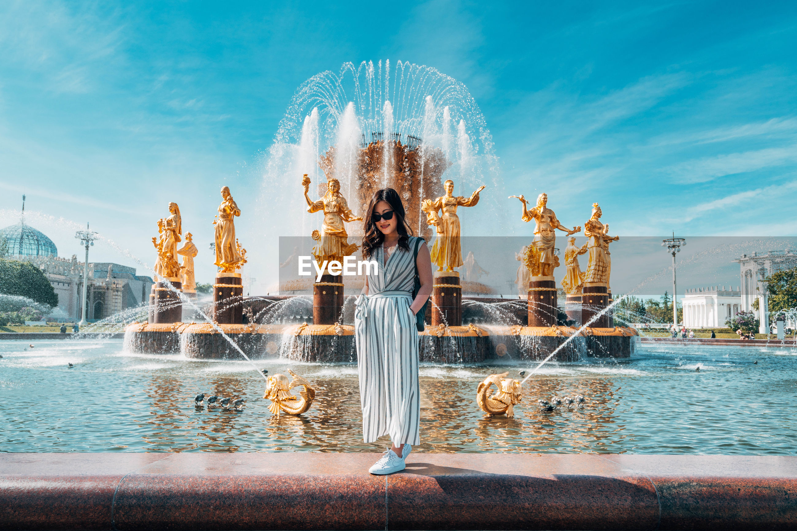 WOMAN STANDING BY FOUNTAIN