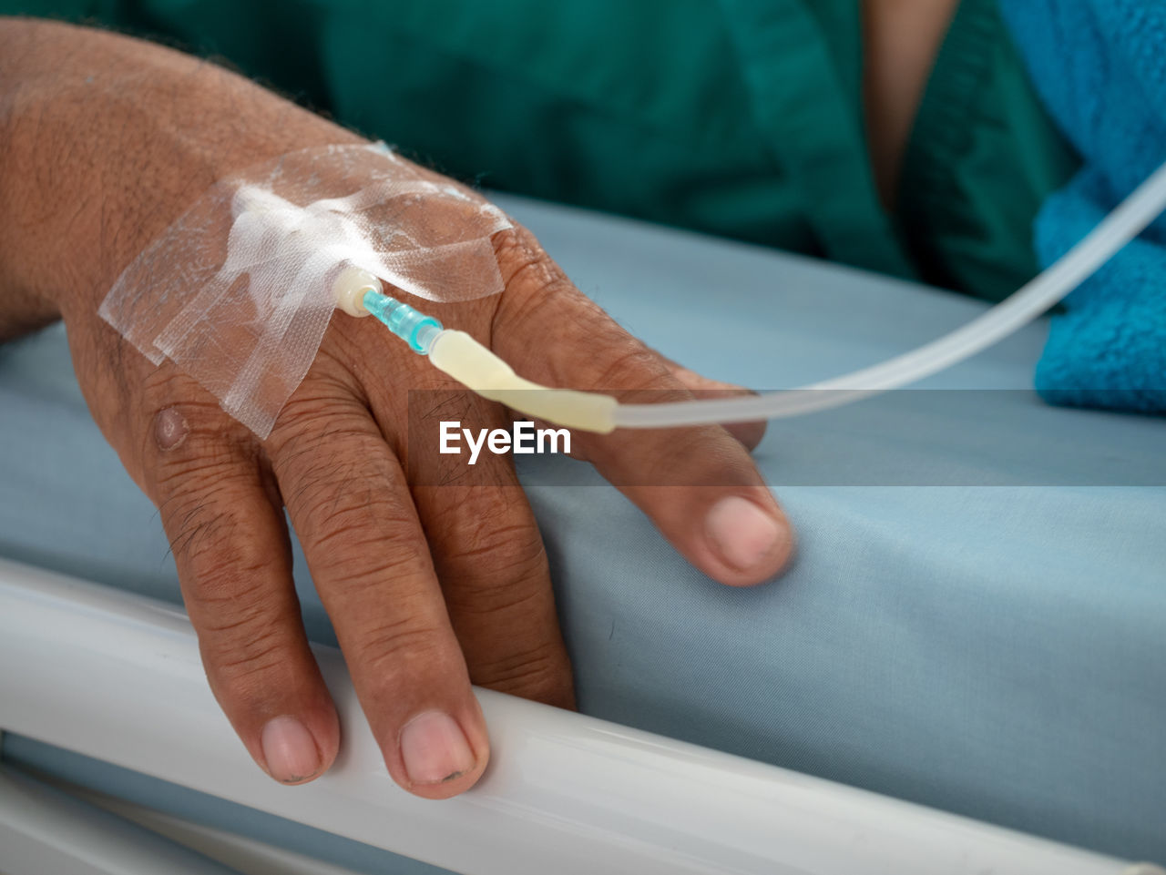 Close-up of human hand with iv drip on bed