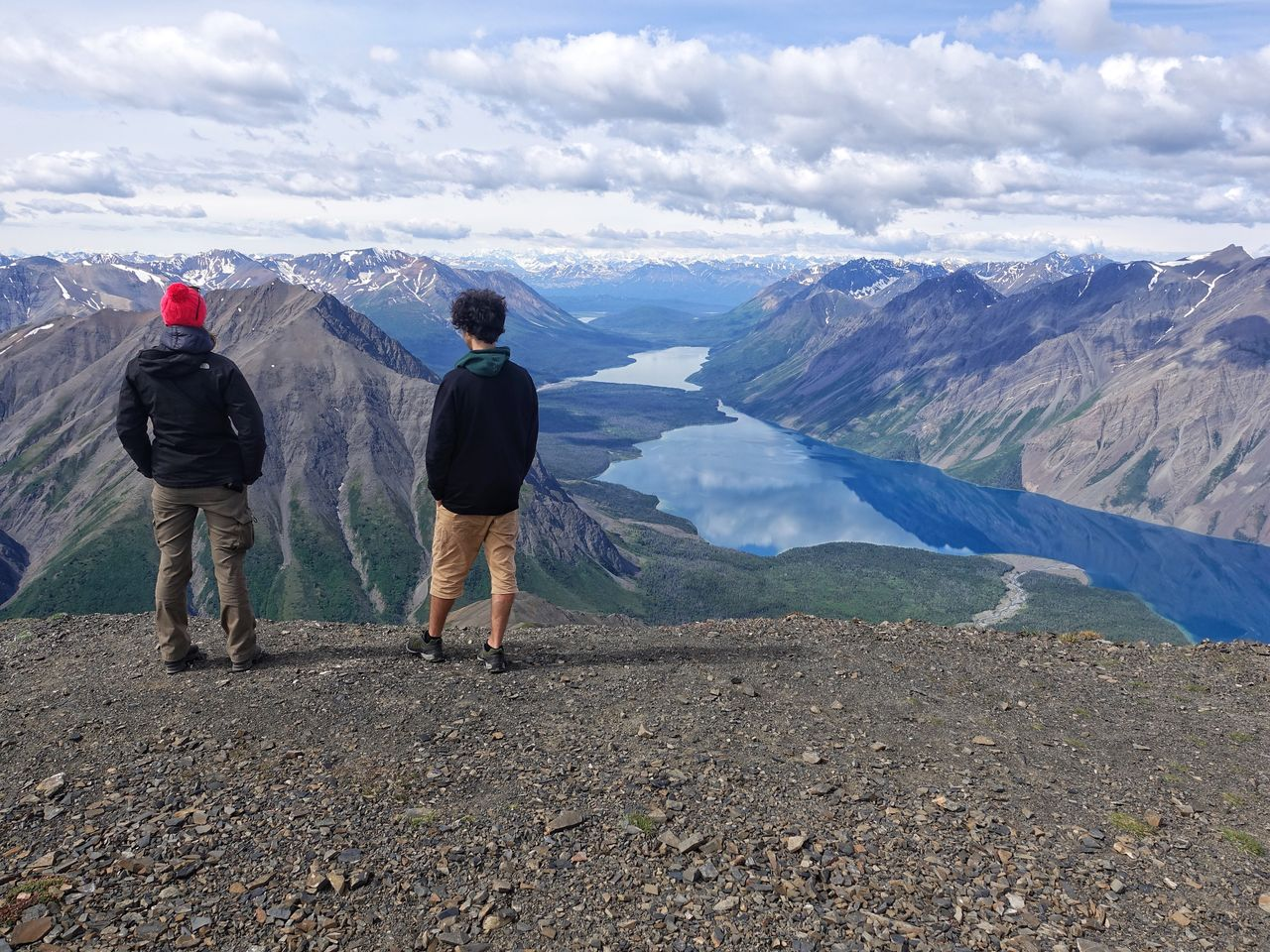 Rear View Of Friends Standing On Mountain Against Valley