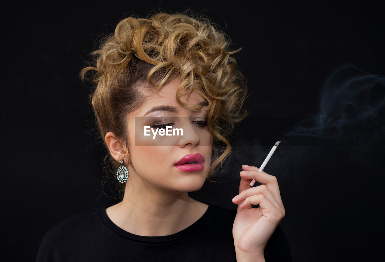 Close-Up Portrait Of Young Woman Smoking Over Black Background
