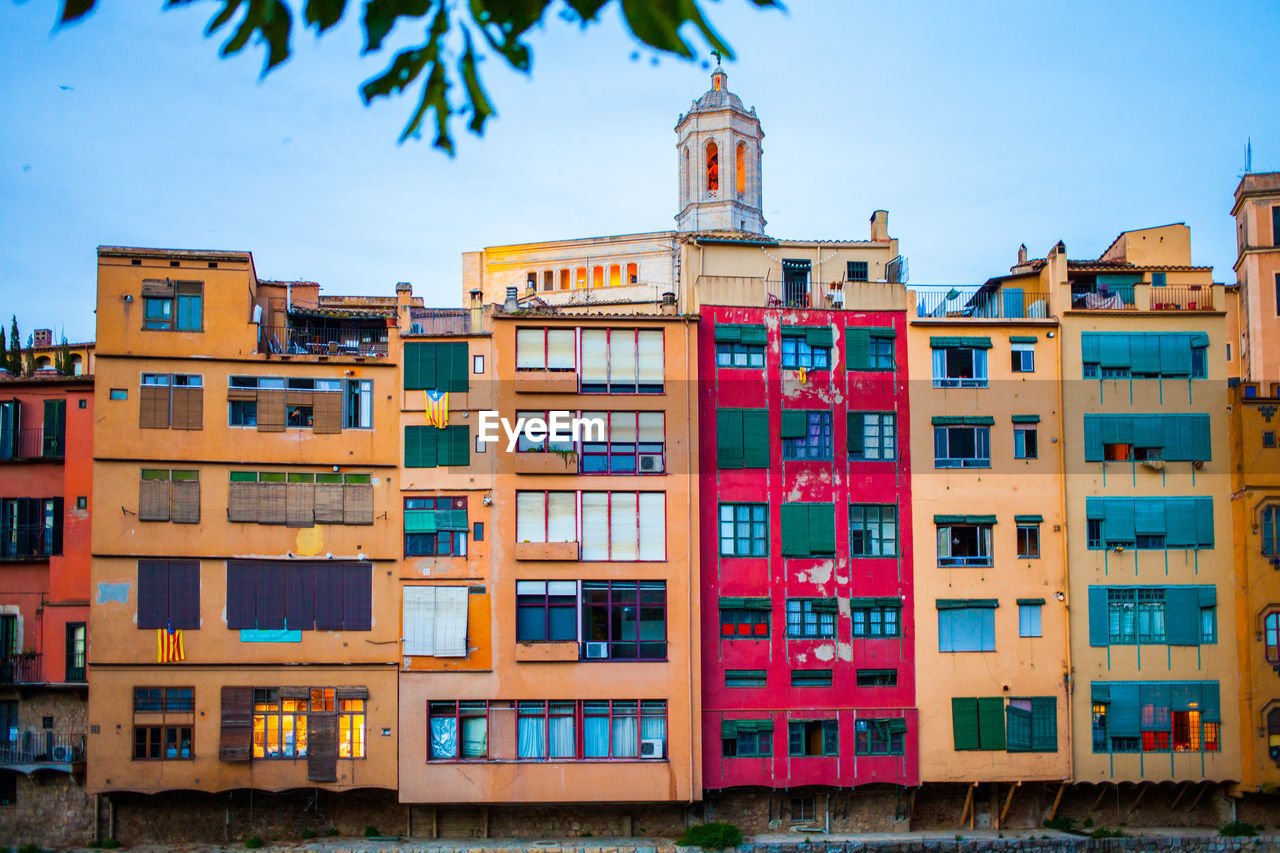 MULTI COLORED RESIDENTIAL BUILDINGS AGAINST SKY
