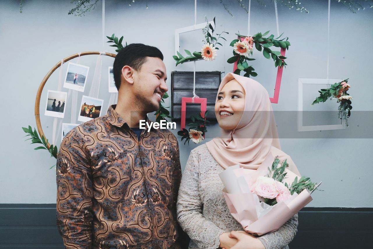 Smiling couple looking at each other while standing against decoration