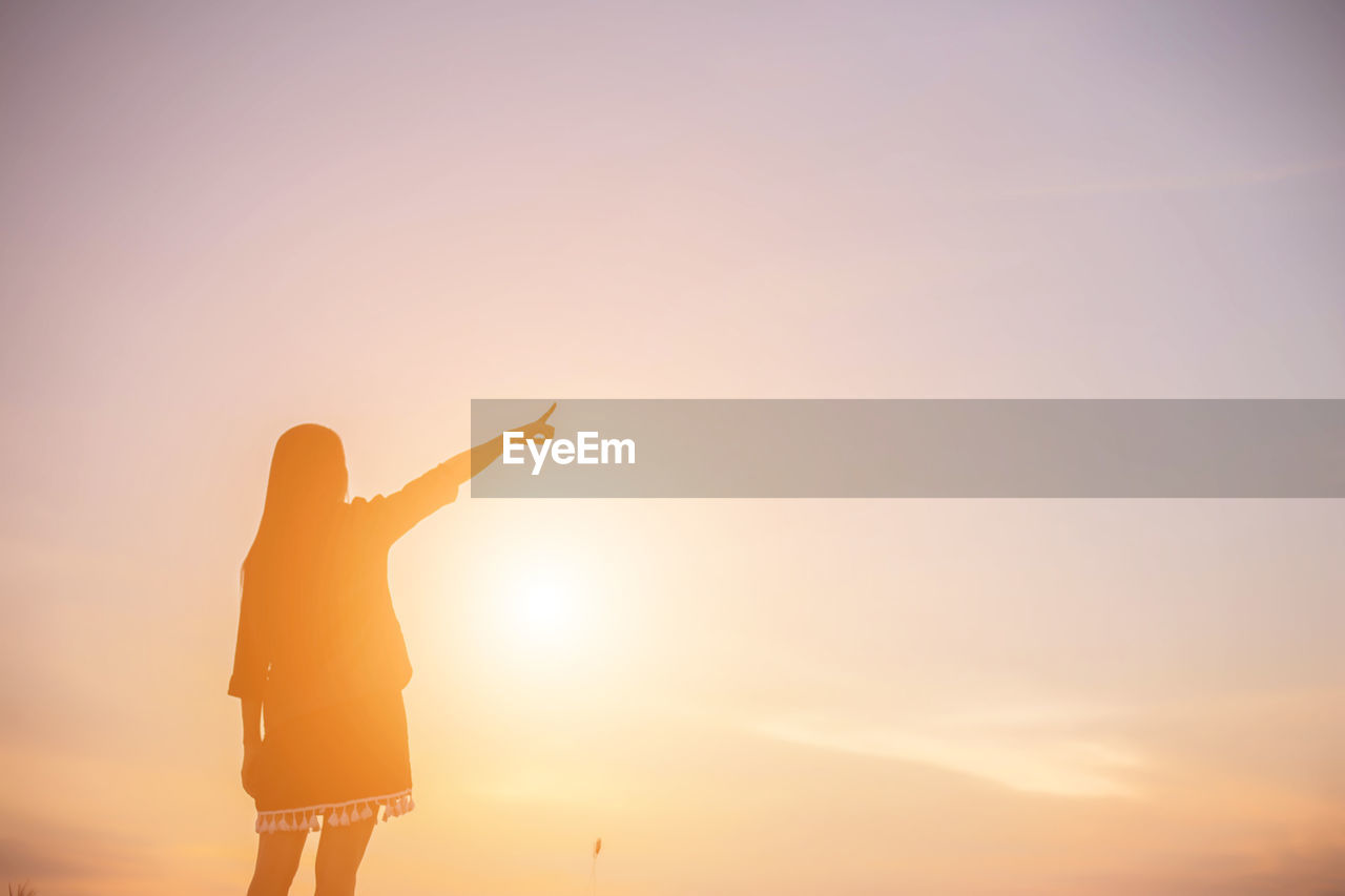 sky, one person, sunset, real people, standing, gesturing, leisure activity, lifestyles, human arm, beauty in nature, nature, silhouette, orange color, arms raised, sun, freedom, copy space, three quarter length, women, outdoors