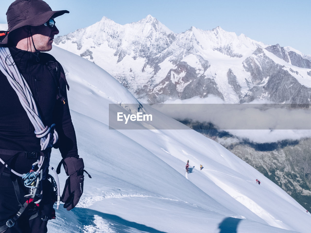 Hiker on snowcapped mountain against sky