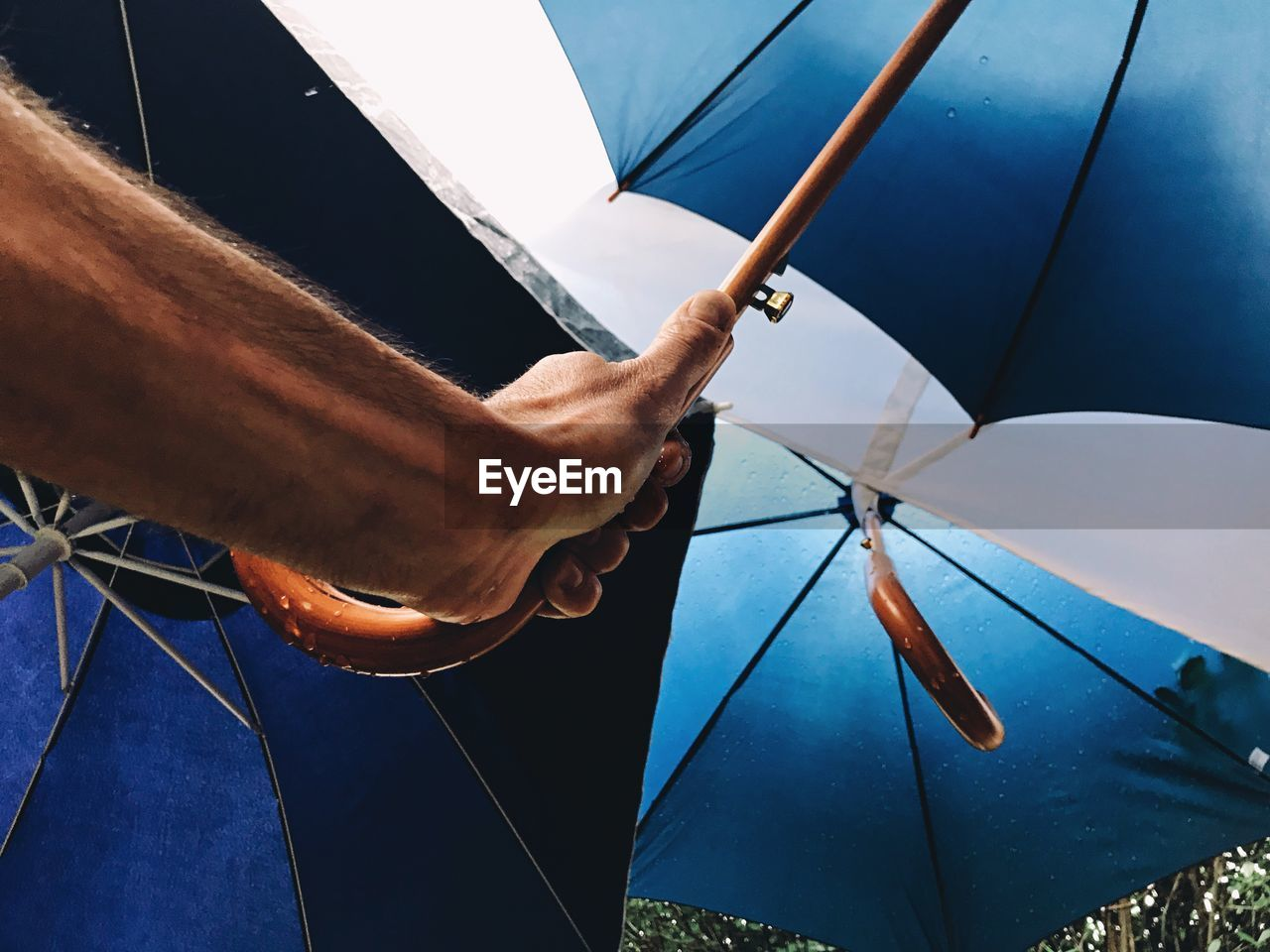 Cropped Image Of Hand Holding Umbrella
