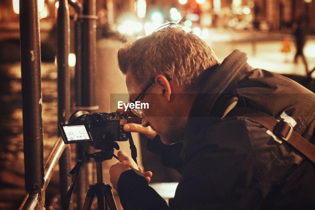 Man photographing through camera at night