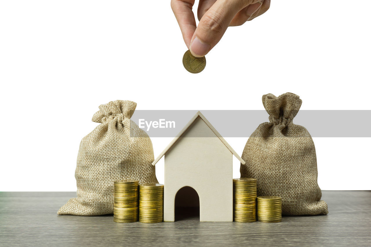 Cropped hand of person holding coin over stack by model home and sacks on table