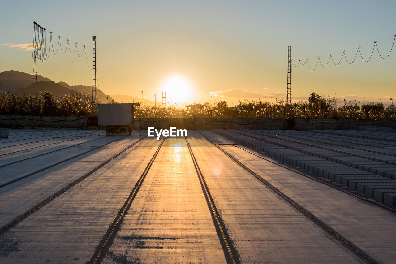sunset, sky, sun, nature, sunlight, beauty in nature, no people, orange color, architecture, built structure, outdoors, scenics - nature, building exterior, the way forward, lens flare, plant, rail transportation, direction, sunbeam, tranquil scene