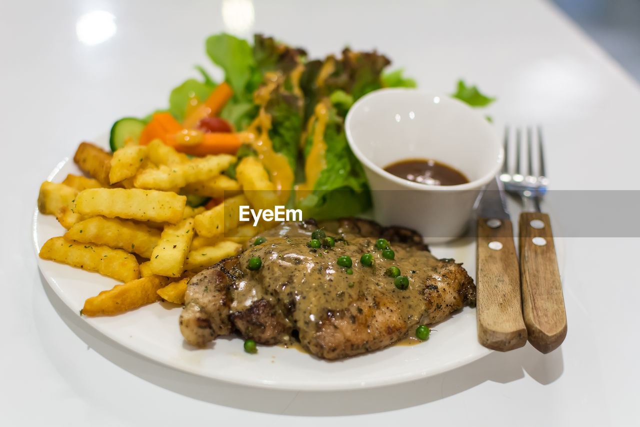 Meat And Curry With French Fries On Plate