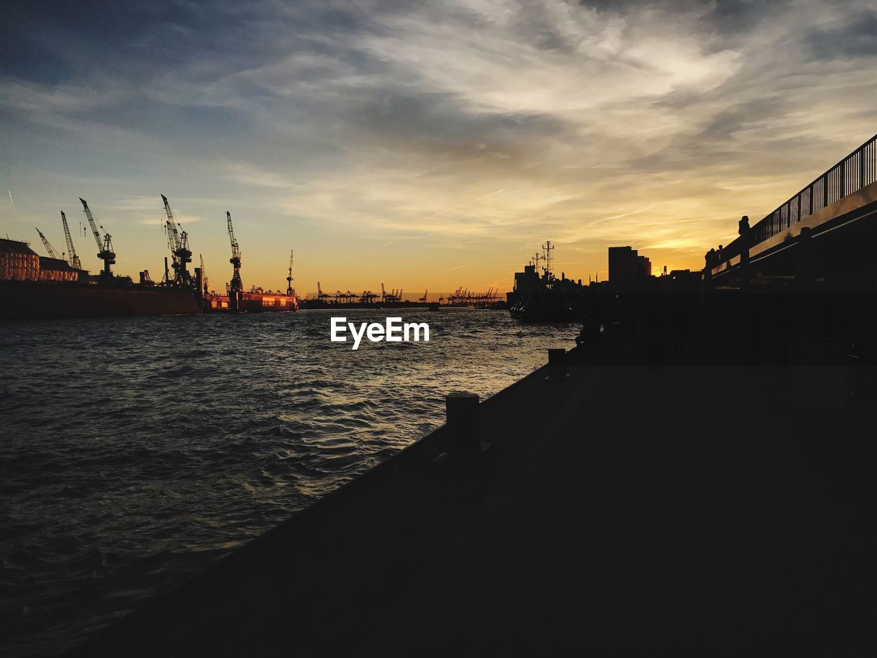 sky, sunset, water, cloud - sky, architecture, crane - construction machinery, built structure, building exterior, nature, sea, machinery, city, no people, transportation, orange color, nautical vessel, freight transportation, silhouette, shipping, outdoors, construction equipment
