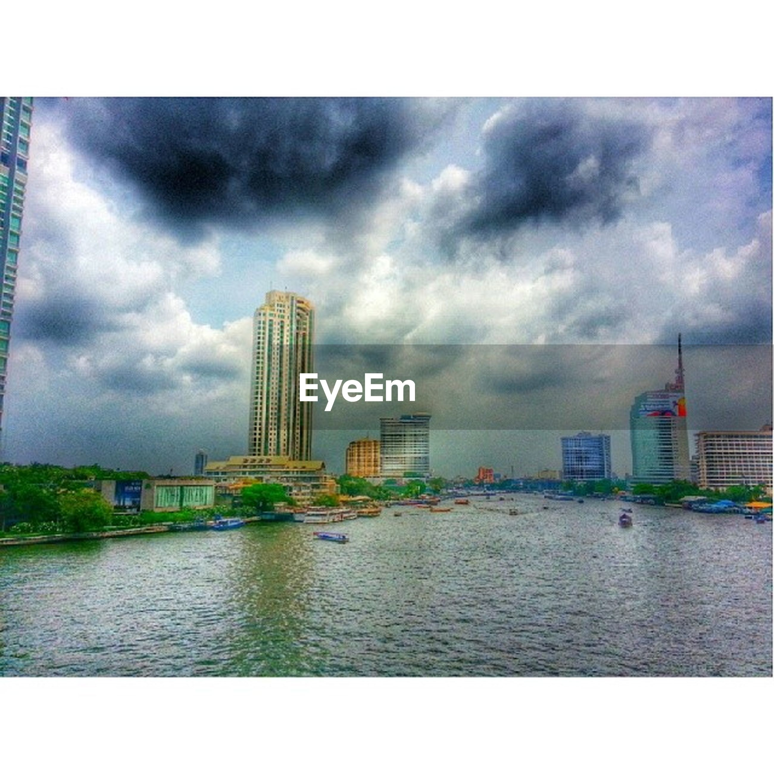 architecture, built structure, sky, building exterior, cloud - sky, cloudy, water, city, transfer print, waterfront, river, weather, overcast, auto post production filter, cloud, tower, storm cloud, travel destinations, skyscraper, tall - high